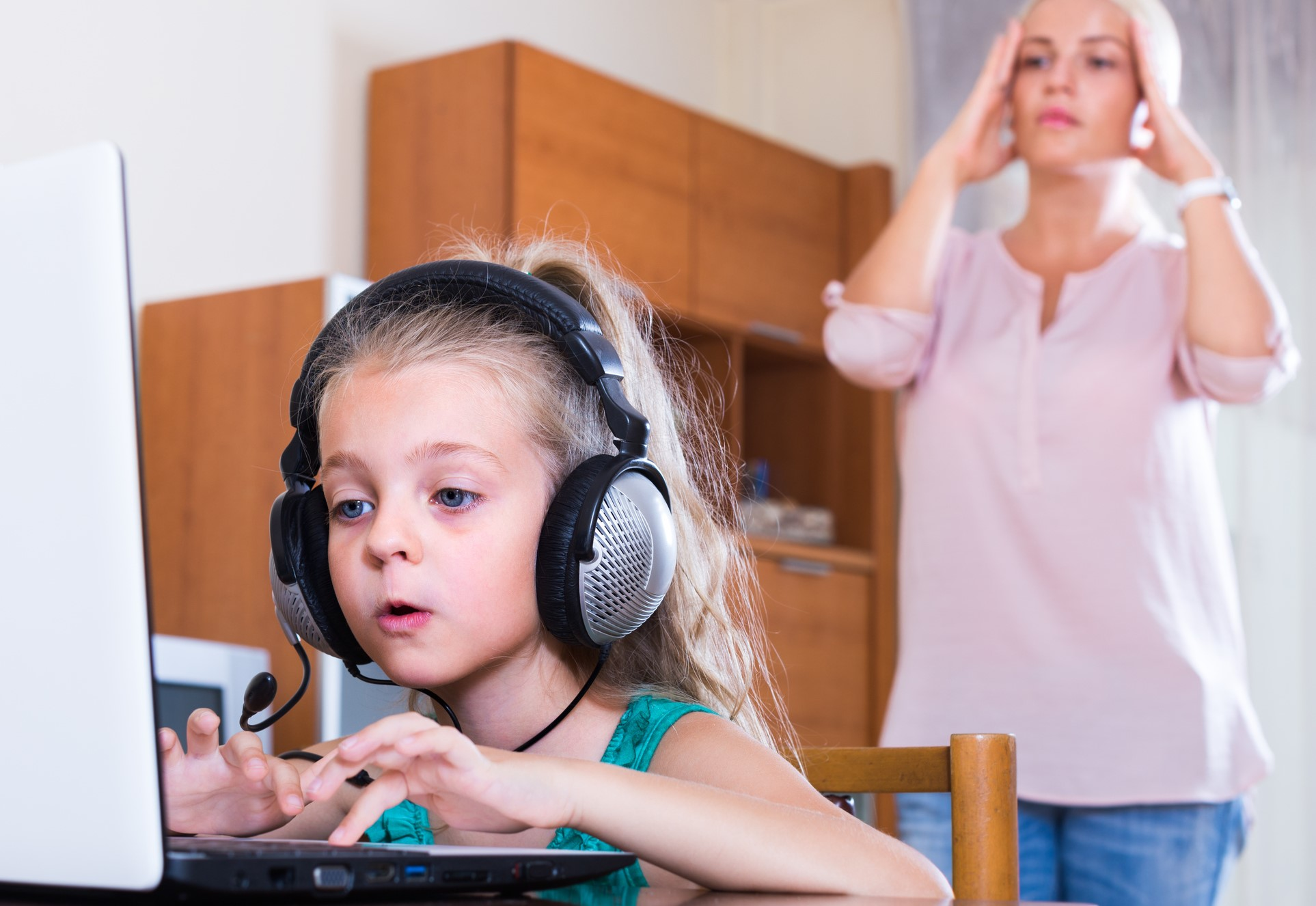 Terrified mother watching daughter using laptop instead of studying