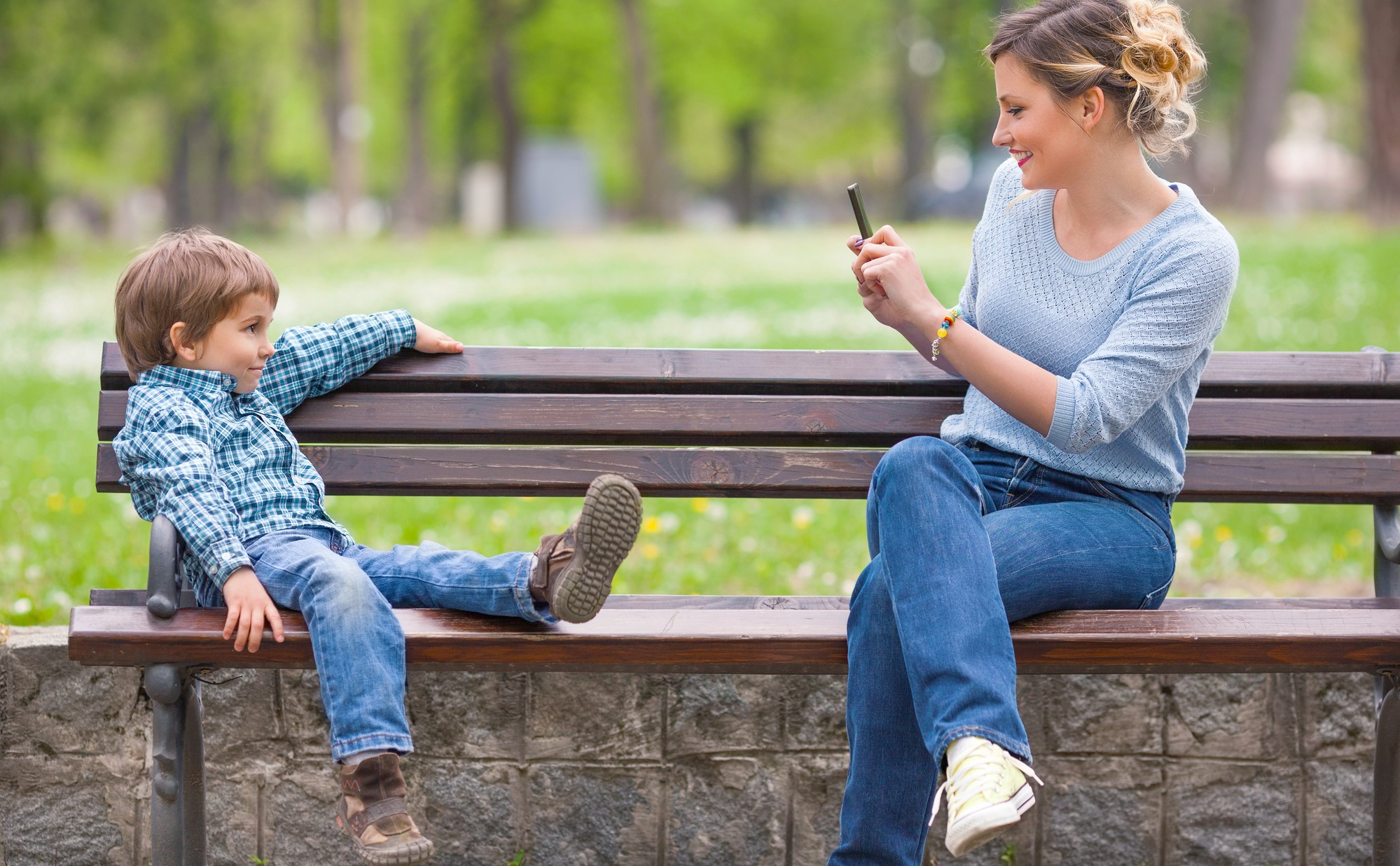 Young mother photographing her cute little son posing on a park bench