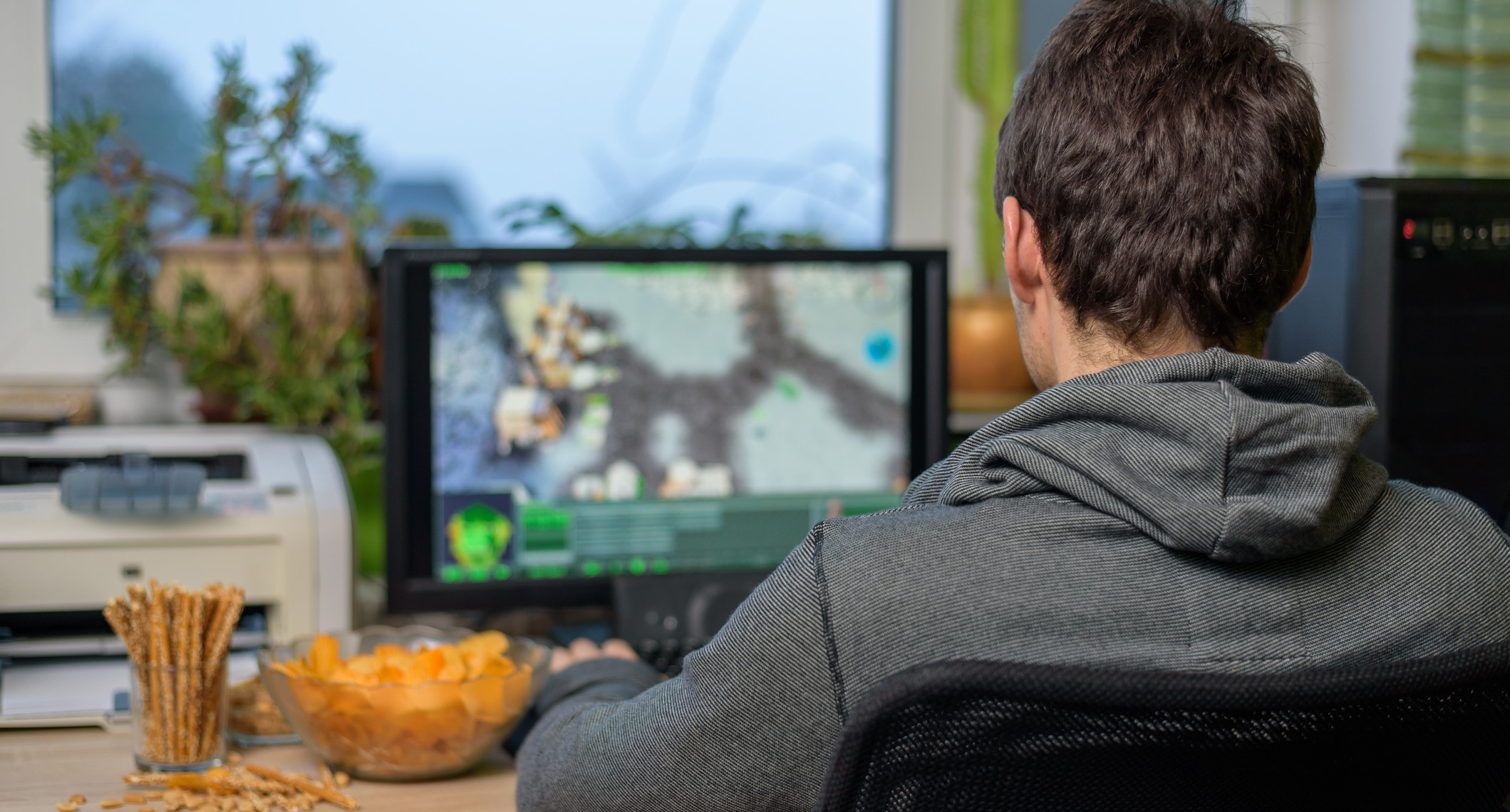 male gamer playing strategy game on computer with snacks lying on table - stock photomale gamer playing strategy game on computer with snacks lying on table - stock photomale gamer playing strategy game on computer with snacks lying on table - stock photo
